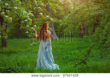 Young beautiful woman in  blooming garden