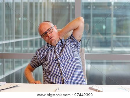 Office male worker suffering from painful tense neck muscles