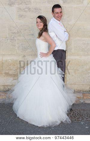 Wedding Pair Hugging And Kissing At The Wall Stone