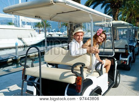Attractive Young Couple Driving Electric Car On A Luxury Waterfront