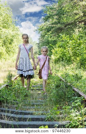 Two sisters walking along railway