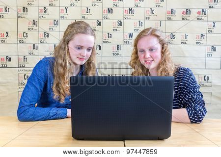 Two Teenage Girls Looking At Computer In Chemistry Lesson