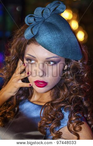 Fashionable beautiful girl in a stylish hat in night club