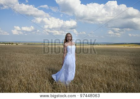 Full length portrait of Young beautiful woman in a long white dress is standing in a wheat field