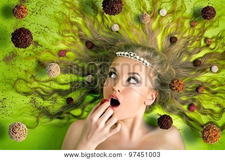 Beautiful woman eating tasty candies on background