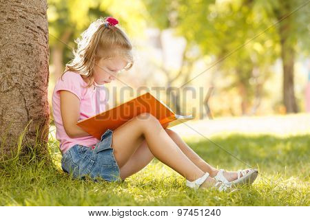 Little Girl Sits Under A Large Tree At The Park And Reads A Book