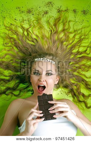 Young attractive woman eating chocolate on background
