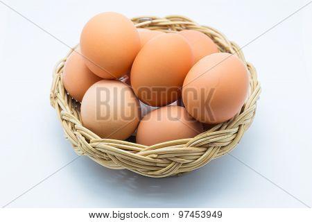 Chicken eggs in a basket on white