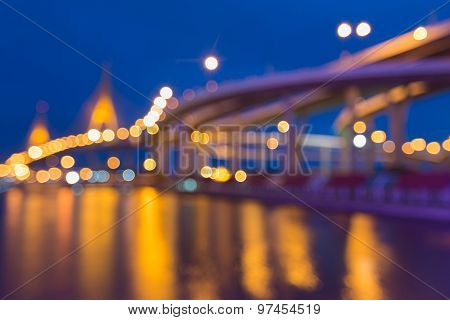 Abstract blurred bokeh light of cross intersection highway and bridge with water reflection