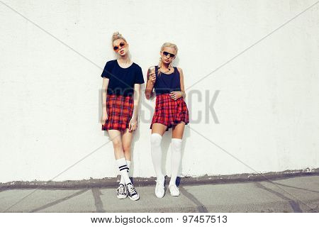 Two Pretty Hipster Sisters Against Urban White Wall