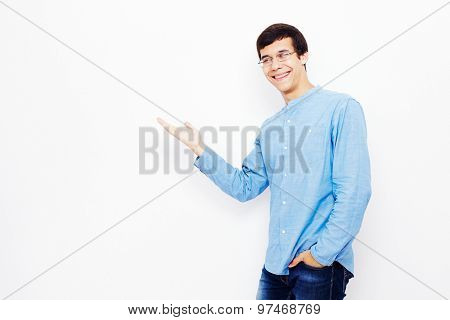 Young hispanic man wearing jeans and glasses smiling and showing his hand at empty space on white wall - presentation concept