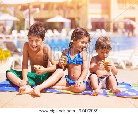 Happy children sitting near the pool and eating croissants, having break after swimming, two cheerful brother and cute sister enjoying summer vacation on beach resort
