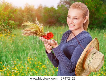 Beautiful farmer girl standing on green floral field in mild sunset light, holding in hands ripe spikelets of wheat and red poppy flowers bouquet, enjoying autumn harvest