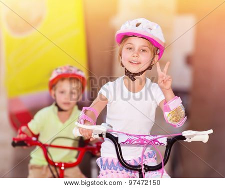 Happy children racing on bicycles, brother and sister organized sports competition, siblings with pleasure playing together, winner girl hand shows the sign of peace