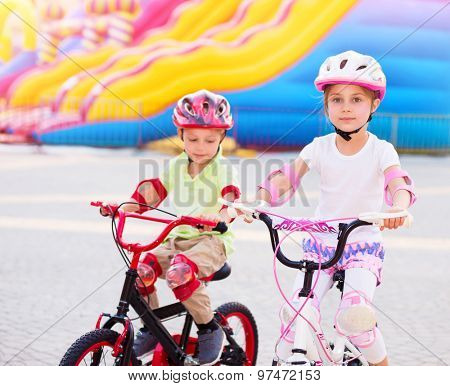 Happy friends on the bicycles, brother with sister having fun in amusement park, playing game outdoors, enjoying friendship and summer holidays