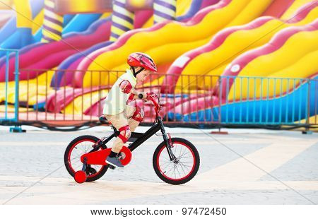 Cheerful little boy riding on the bicycle in amusement park, happy carefree childhood, having fun outdoors in summer camp