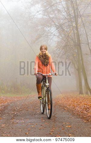 Happy Active Woman Riding Bike In Autumn Park.