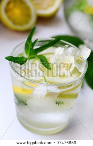 Glass of cold refreshing summer drink with mint and slices of lemon on table close up