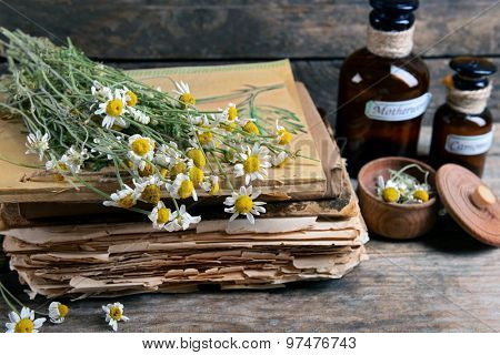 Old books with dry flowers and bottles on table close up