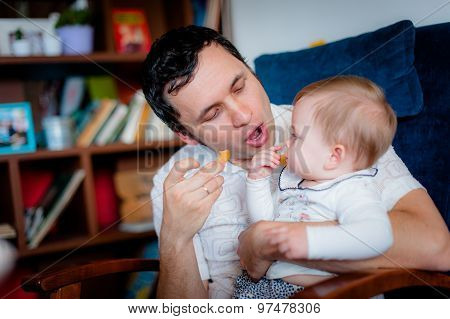 Image of cute little daughter in young dad's hands
