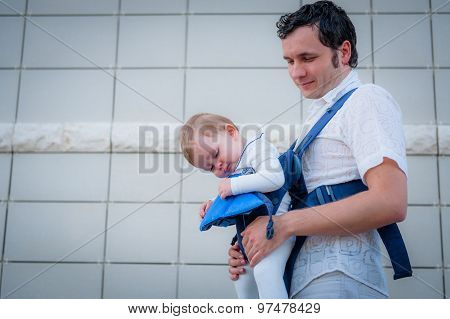 Father and his asleep baby walking in a baby carrier in city