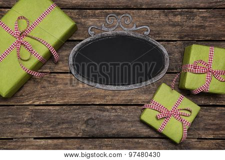 Christmas presents wrapped in green paper with red white checked ribbon on old wooden background with a tin sign.