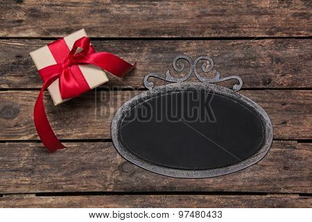Old tin frame with a red christmas present on old wooden background.