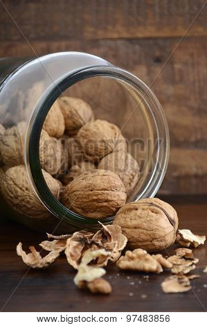 Walnuts In Glass Jar On Wood Table.