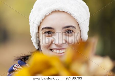 Headshot of a beautiful woman at the autumn park