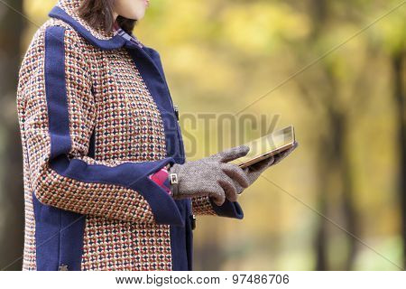 Woman using a tablet computer at the park