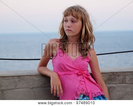 Girl stands on a sea embankment