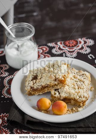 Two Slices Of Apricot Pie On A White Plate And Natural Yogurt In A Glass Jar On Brown Fabric, Vintag