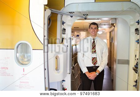 MOSCOW - DECEMBER 10, 2014: handsome Emirates crew member meet passengers. Emirates handles major part of passenger traffic and aircraft movements at the airport.
