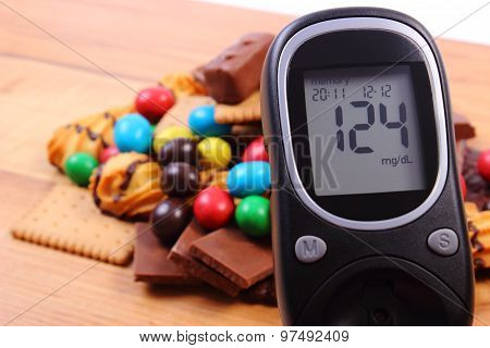 Glucometer With Heap Of Sweets On Wooden Surface, Diabetes And Unhealthy Food