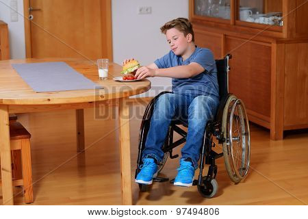 Smiling Disabled Boy In Wheelchair Is Eating