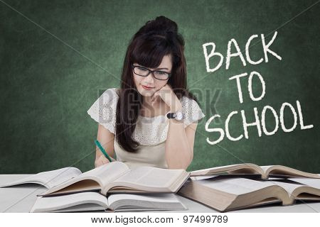 Female Student Back To School And Write On Book