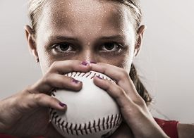 image of softball  - Softball girl holding ball with eyes looking above - JPG