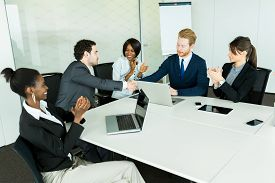 picture of applause  - Business deal made between two businessmen in a neat office envrionment followed by a round of applause - JPG