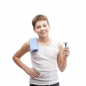 foto of shoulder-blade  - Happy young boy in a sleeveless white shirt with a towel over his shoulder and and a shaving razor blade in his hand - JPG