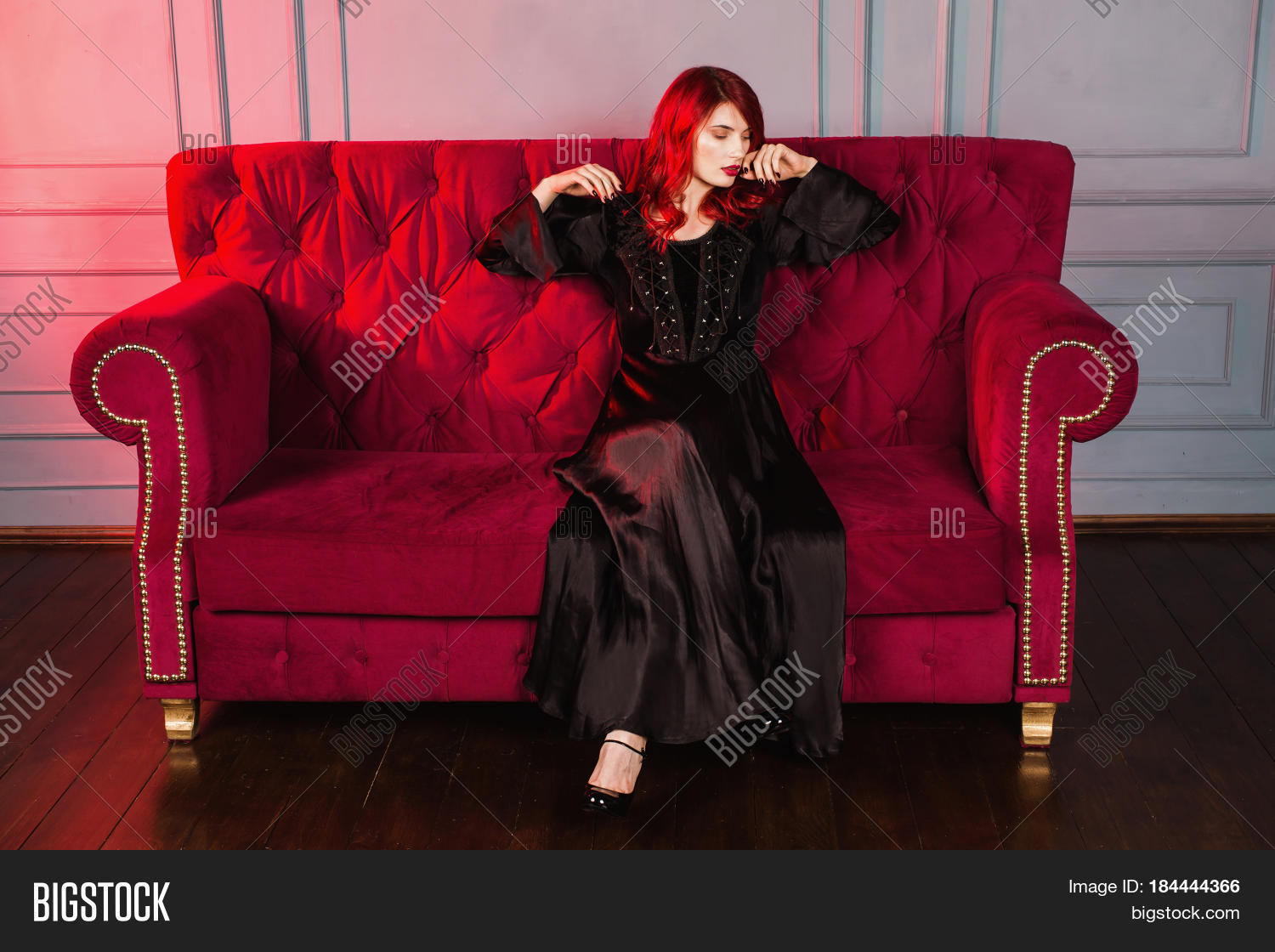 Beautiful glamour girl with red hair and natural make-up and pale skin. A  glamour woman in a black retro glamour dress sitting on a red couch.
