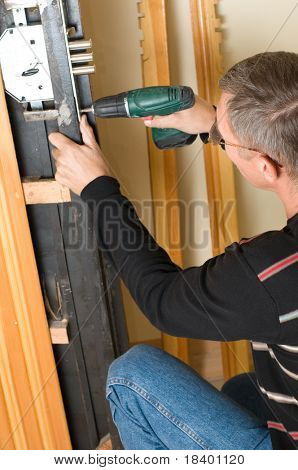handyman repairing lock with drill