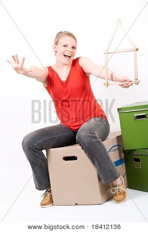 Young Woman With A House Symbol Sits On Moving Box