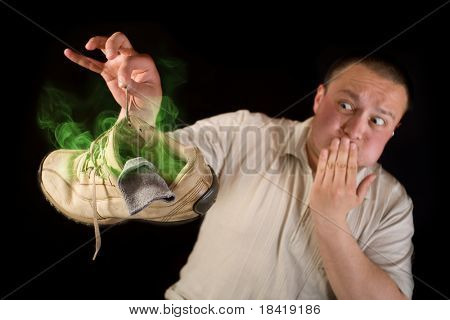 Shocked man holding smelling shoe isolated on black background