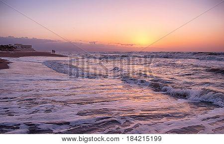 Hora dorada en la playa, donde se observa a lo lejos una pareja paseando por la orilla.