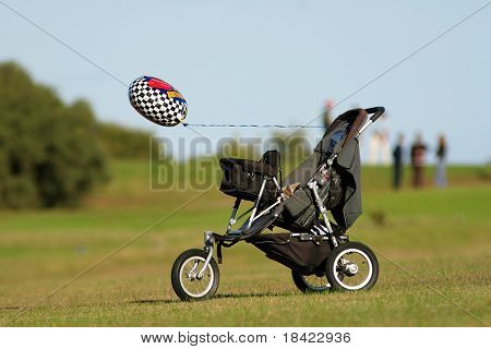 Pram with balloon on the grass