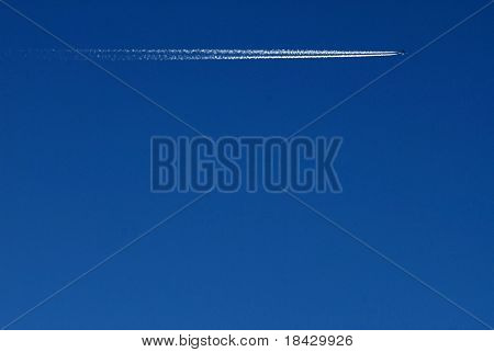 Passenger jet plane on clear, blue sky. Vapor traces parallel to the image edge.