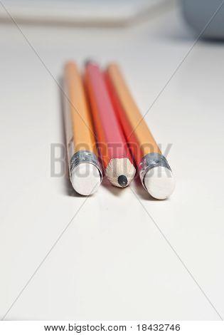 Three pencils lying on an office desk