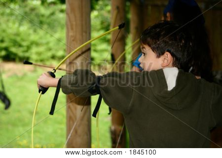 Young Boy Poised With Bow And Arrow