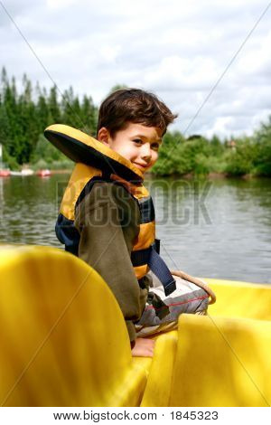 Boy In Life Vest Enjoying The Pedalo
