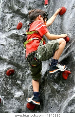 Boy Enjoying The Indoor Rock Climbing